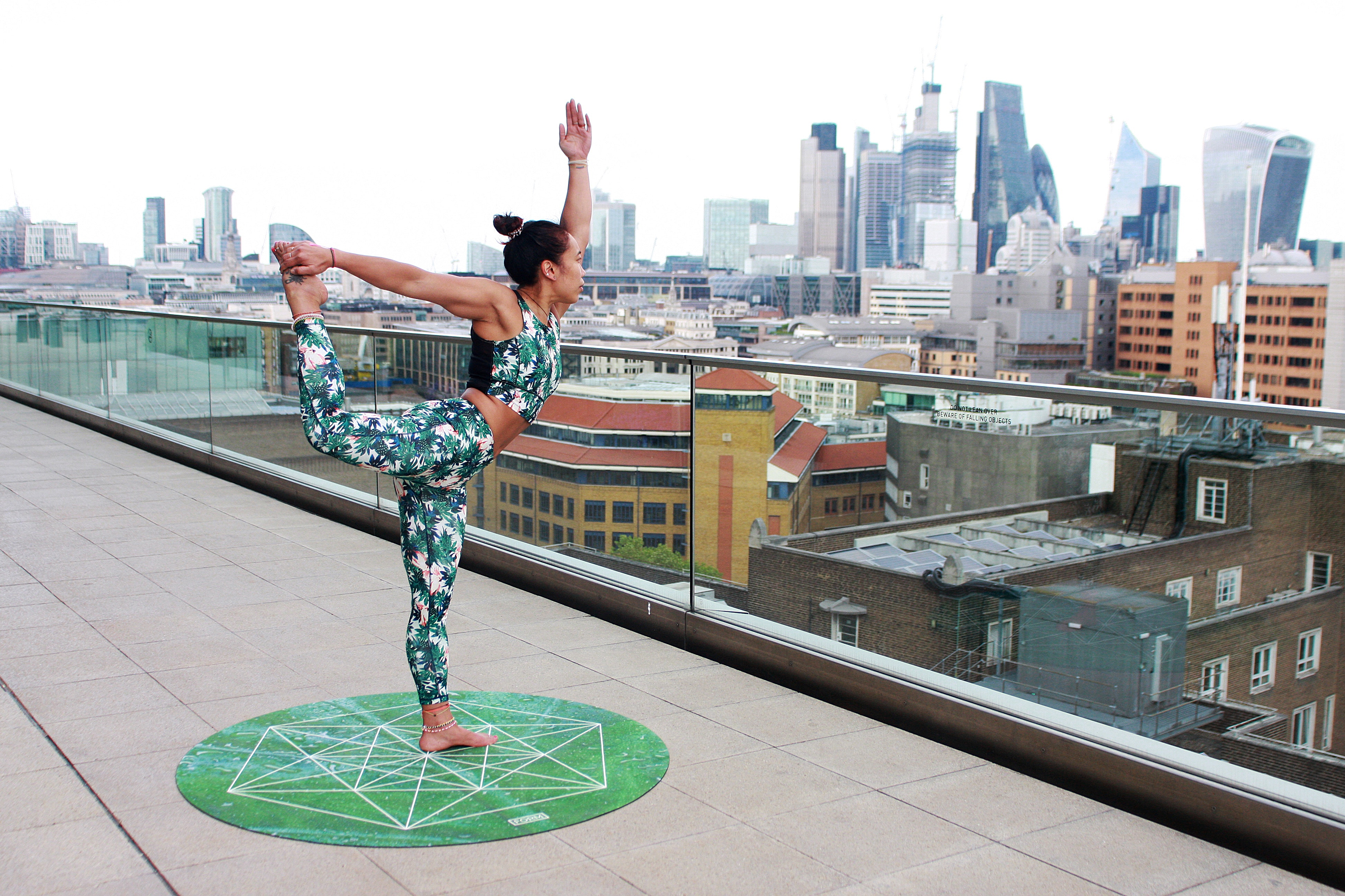 woman-on-round-green-yoga-mat-position-in-right-leg-high-and-1139483